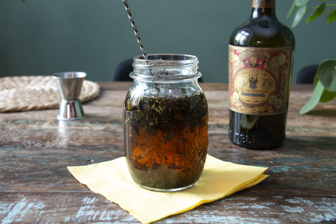 A mason jar on a table filled with earl grey loose tea leaves and sweet vermouth, with a bar spoon inside. In the background is a bottle of sweet vermouth and a jigger.