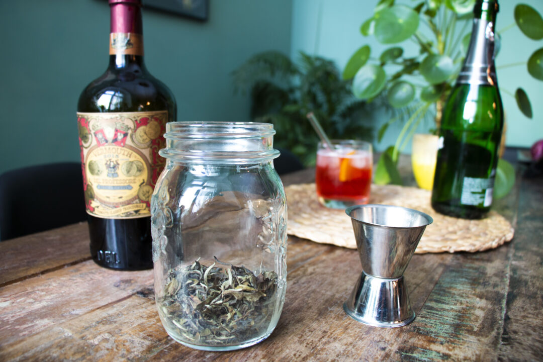 A table with a bottle of sweet vermouth, a mason jar with dry earl grey tea leaves, a jigger in the foreground and a bottle of prosecco, a Caffo Spritz cocktail and a plant in the background.