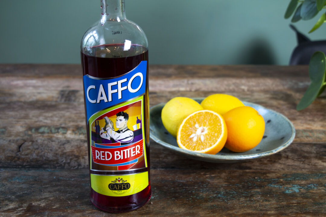 A bottle of Caffo Bitter Red liqueur on a table with a plate of fresh oranges next to it.
