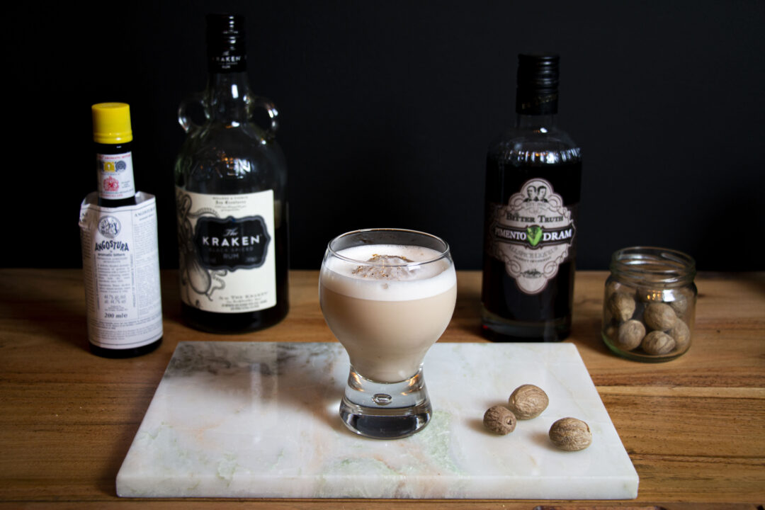 A straight on shot of The Orb cocktail with a bottle of Kraken rum, Pimento Dram, Angostura bitters, and a jar of whole nutmeg seeds