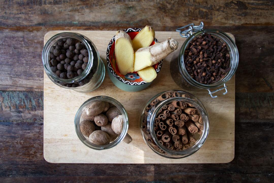 Looking overhead, there are 5 jars of spices - whole cinnamon sticks, cloves, allspice, nutmeg and fresh ginger