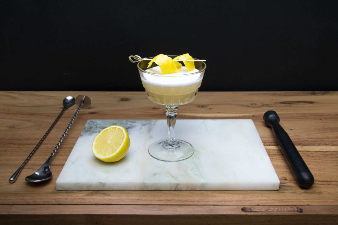 The BBW cocktail in a vintage stem glass, sitting on top of a white marble cutting board with stirring spoons and a muddler next to it. The cocktail has a fancy lemon peep garnish and foam on top.