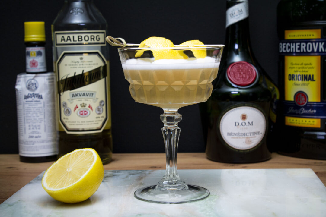 A straight on shot of the BBW cocktail. It is clear and yellowish with a foamy top. It's in a vintage stem glass sitting on a white marble cutting board. In the background are the ingredients - a bottle of Angostura bitters, Akvavit, Benedictine and Becherovka