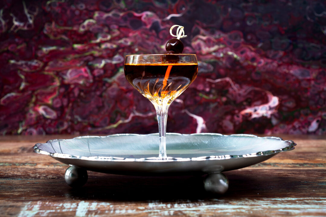A straight on shot of a Manhattan cocktail on a raised serving train with a swirly purple background