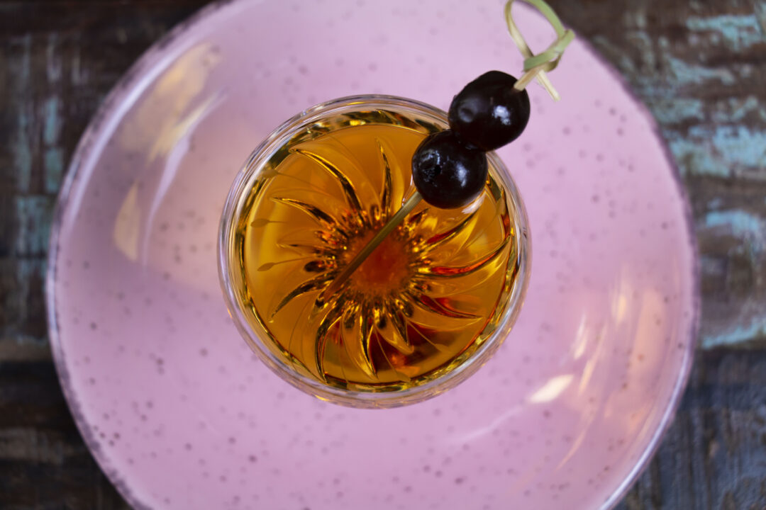 An overhead shot of a Manhattan cocktail in a fancy glass with two amarena cherries