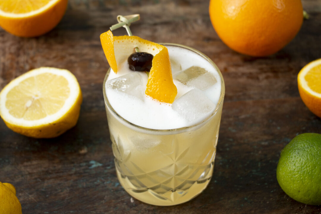 A close up photo of a whiskey sour cocktail with and orange peel and amarena cherry garnish. The cocktail is fresh and foamy. Around the cocktail are oranges, limes and lemons.