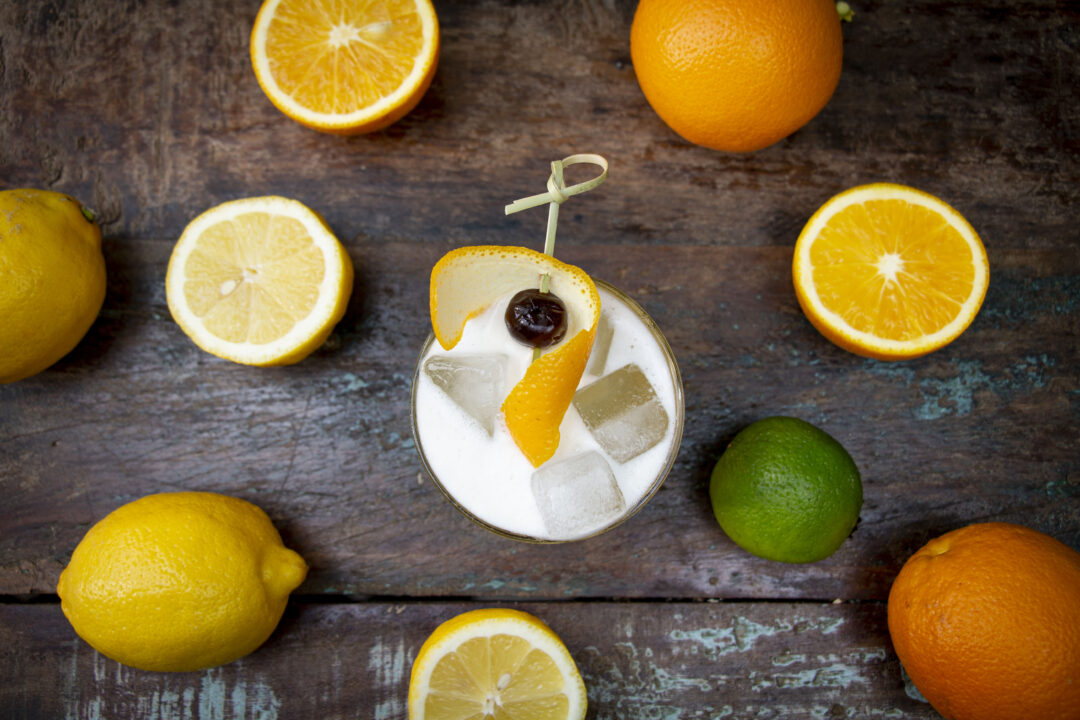 An overhead shot of a whiskey sour cocktail with a foamy head and an amarena cherry garnish and orange peel. Around the cocktail are oranges, lemons and limes.