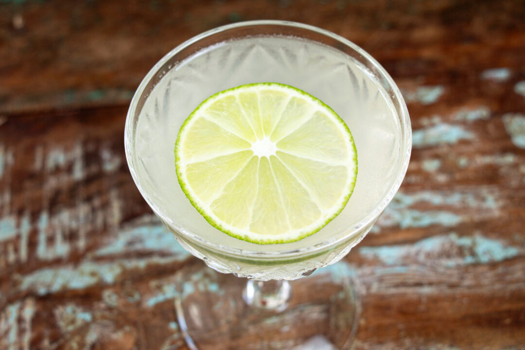 An overhead shot of a gimlet cocktail with a lime slice garnish