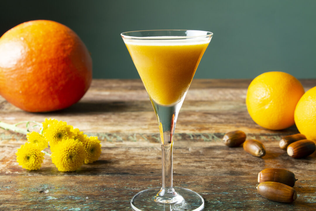 A straight on shot of a pumpkin cocktail in a stem glass with oranges, chestnuts and yellow flowers