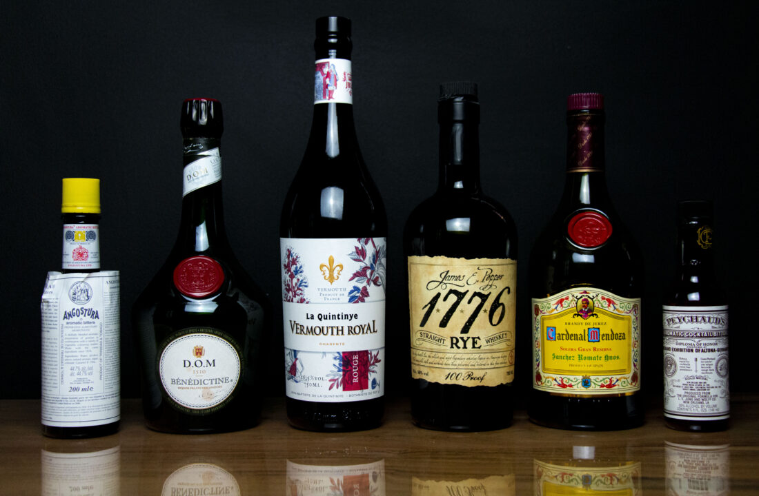 A photo of 6 bottles - rye whiskey, sweet vermouth, brandy, angostura bitters, peychaud's bitters and Benedictine