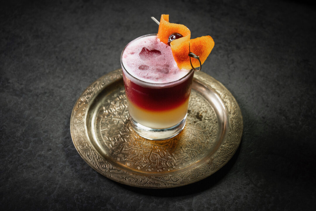 A New York Sour cocktail on a bronze platter on a counter top with an orange garnish and amarena cherry