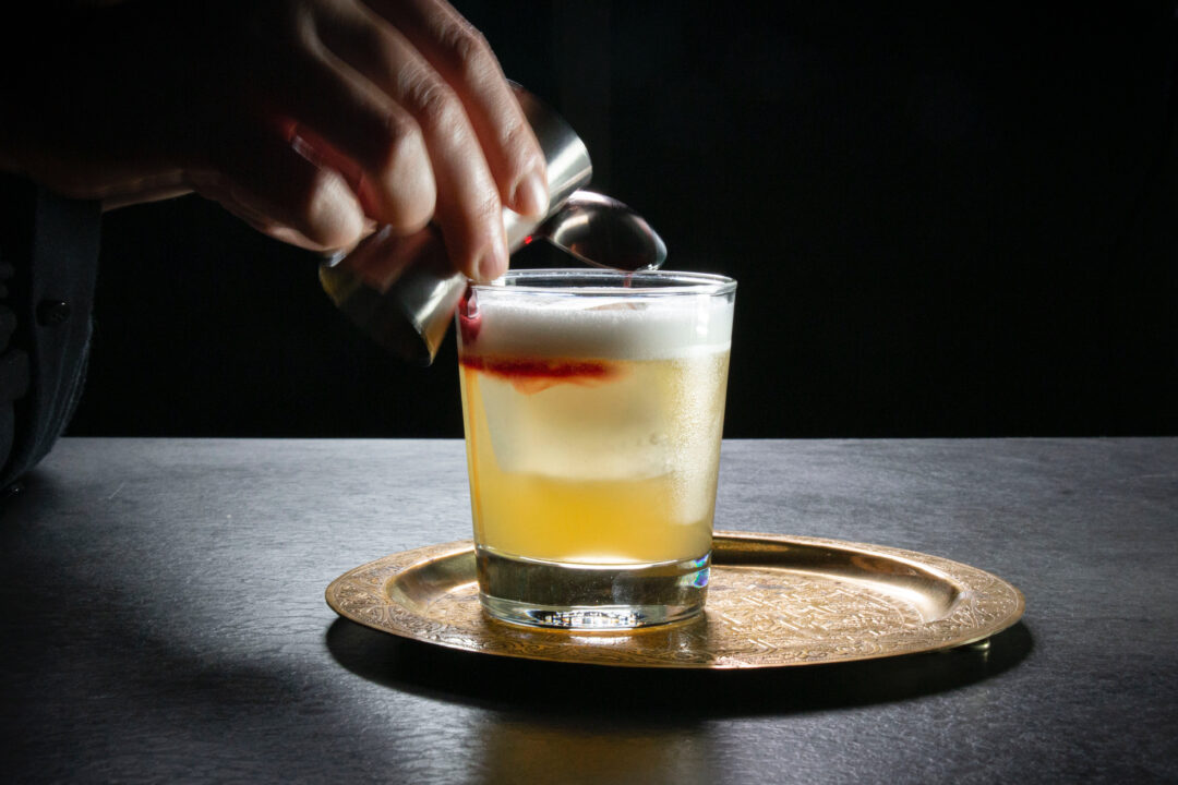 A motion shot of red wine being poured over an upside down spoon on top of a whiskey sour cocktail
