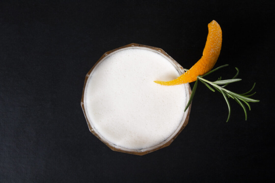 An overhead shot of a cocktail glass on a black background with an orange peel and rosemary sprig garnish